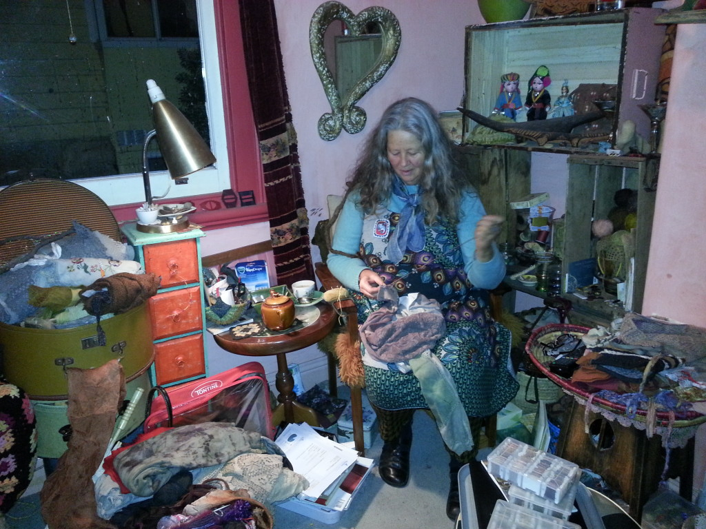 Kate stitching in her studio filled with natural and found treasures